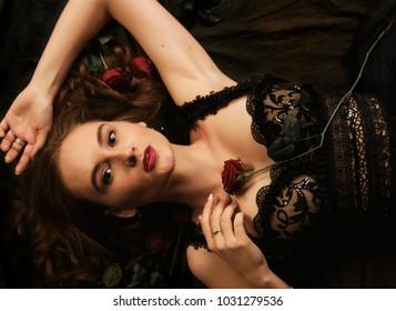 Beautiful girl in a black dress with flowers in her hands. Studio shot, dark background.