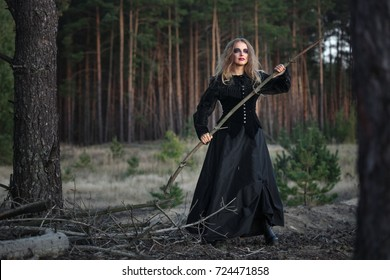 beautiful girl in a black dress in the forest