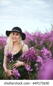 beautiful girl in black dress and hat standing in a field of lupine flowers