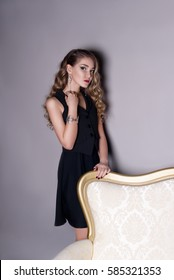 beautiful girl in a black dress on a gray background at the beautiful golden sofa jewelry shows