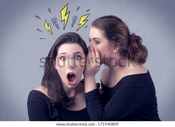 A beautiful girl in black dress sharing secrets to her girlfriend concept with drawn energetic electric yellow signs above her head on the wall background.