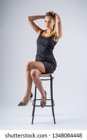 Beautiful girl in a black dress sitting on a high chair