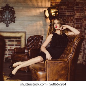 beautiful girl in black dress sitting on a leather couch