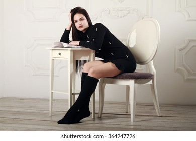 Beautiful girl in a black dress and black socks sitting on a chair in a bright room.