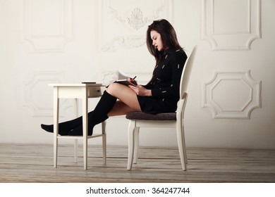 Beautiful girl in a black dress and black socks sitting on a chair in a bright room and makes notes in a notebook.