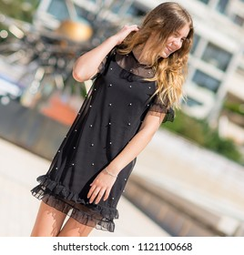 A beautiful girl in a black dress is standing and dreaming against the background of France