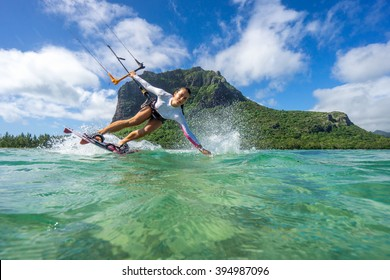 Beautiful girl with black hair kiting in the clear waters of the Indian Ocean on the background of clouds and high mountains.