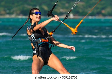 Beautiful girl with black hair kiting in the clear waters of the Indian Ocean. Mauritius