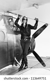 Beautiful girl in black jacket standing on a war aircraft. Retro black and white photo.