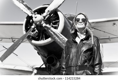 Beautiful girl in black jacket standing next a war aircraft. Retro black and white photo.