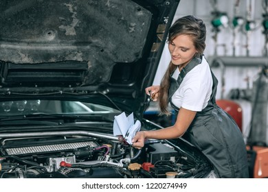 A beautiful girl in a black jumpsuit and a white t-shirt is smiling, checking the oil level in a black car in the garage.