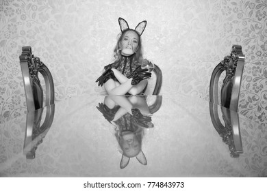 beautiful girl in black lace rabbit mask, leather short gloves with bows and guipure neck corset sitting at a table with drink alone