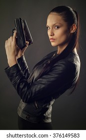 Beautiful girl in black leather jacket posing with two pistols in their hands.