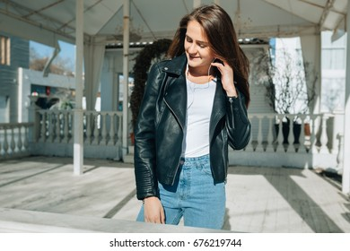 The beautiful girl in a black leather jacket and a light t-shirt listens to music in white earphones. She gently looks aside and wind develops her hair in an opposite direction. Sunshine heat the girl