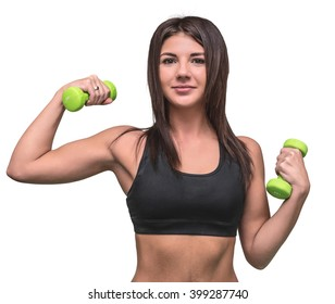Beautiful girl in black sportswear is doing exercises with green dumbbells on a white background