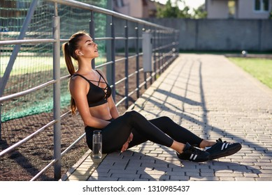 A beautiful girl in black sportswear listening to music with wireless headphones while training on an outdoors sports ground. Sports concept.