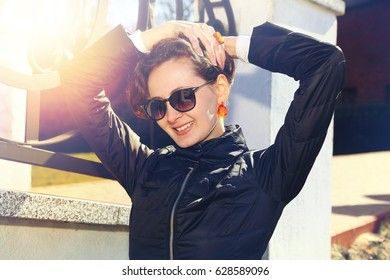 A beautiful girl in black sunglasses and amber. Smiled brunette model with amber decorations on the street with the effect of sunlight. A yellow light filter on the smiling model. Toned photo