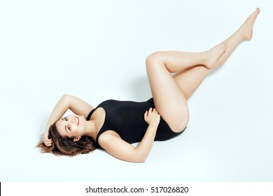 Beautiful girl in black swimsuit on a white background. She lies on her back and smiling