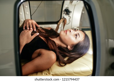 beautiful girl in a black T-shirt and white pants lies in a hyperbaric chamber