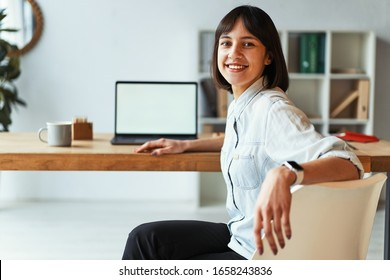 Beautiful girl blogger looking at camera and smiling while using laptop and smart watch. Graphic designer is happy to working on interesting project in modern office. Mockup concept