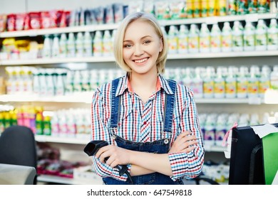 Beautiful girl with blond hair wearing working suit standing at cash register and smiling, products at background, supermarket concept.