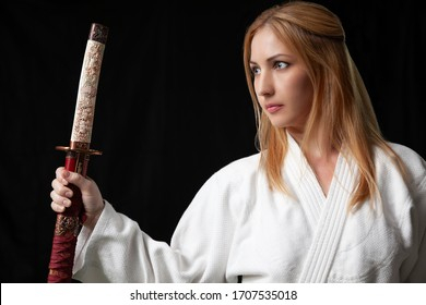 Beautiful girl with blond hair in white kimono holds a Japanese katana sword against a black background