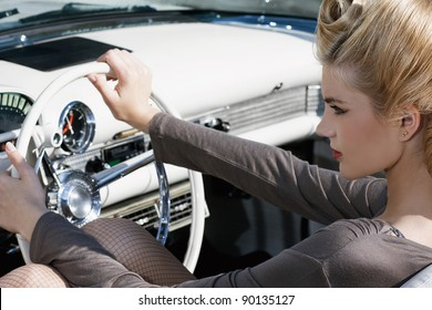 The beautiful girl, blond with visage and hair-up, sits in the old car. Wheel, dashboard, chrome.
