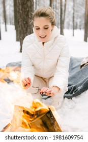 A beautiful girl, a blonde European woman in warm winter clothes, sits and warms her hands by a burning fire in a snowy forest. The concept of rest and vacations in the winter season.