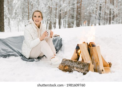 A beautiful girl, a blonde European woman in warm winter clothes, sits and warms herself by a burning fire in a snowy forest. The concept of rest and vacations in the winter season.
