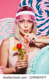 Beautiful girl with blonde hair wearing top and pink cap standing with huge sweet lollypops at pink background, candy lover, drinking lemonade.