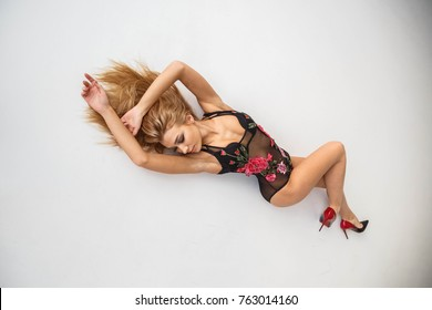 Beautiful girl blonde in sexy black lingerie posing at Studio about the wall