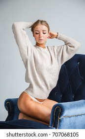Beautiful girl blonde in underwear, sweater posing on white background, sitting in a chair