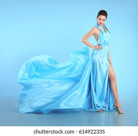 9322ac24e49 Beautiful Girl in blowing blue dress. Woman in Flying Gown