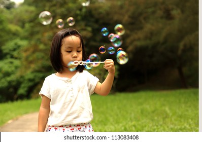 Beautiful girl is blowing bubbles in garden. Isolated on green field background.