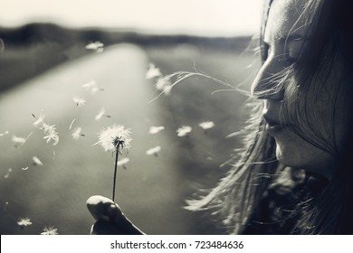 Beautiful girl blowing dandelion in black and white