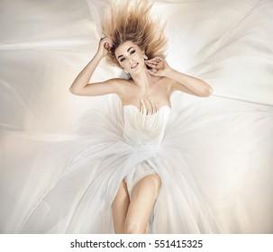 Beautiful girl in blowing dress flying