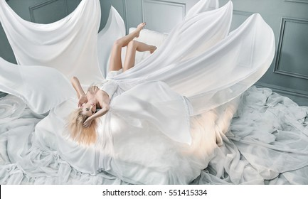 Beautiful girl in blowing dress flying over bed