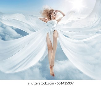 Beautiful girl in blowing dress flying over clouds