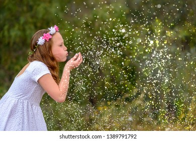 Beautiful girl blowing magic stars in her hand. Little child with wearing flower wreath blowing magical rainbow glitter sparkles in the air for a celebration, happiness or party idea.