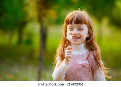 beautiful girl blowing on white dandelion, smile
