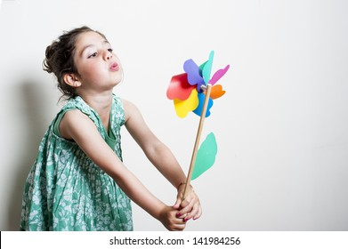 beautiful girl blowing a plastic windmill