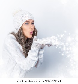 beautiful girl blows off snowflakes from hands