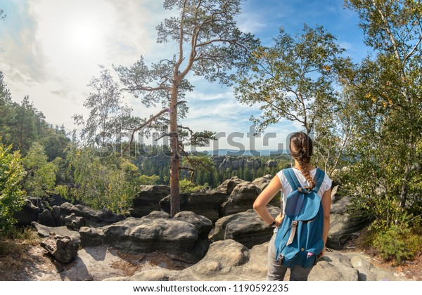 Beautiful girl with a blue backpack at the top of a mountain, Saxon Switzerland, great view at the Schrammsteine