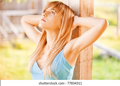 Beautiful girl in blue dress leans against wooden column and looks upwards.