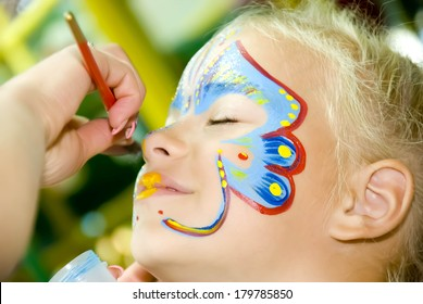 Beautiful girl with blue eyes with painted butterfly on her face