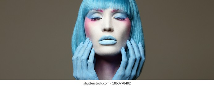 Beautiful girl with Blue Hair, hands and art make-up. Fairy beauty young woman