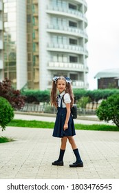 a beautiful girl, in a blue school uniform, with a school backpack, near the school building. Return to school, September 1