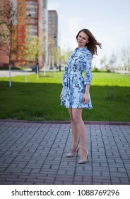 The beautiful girl in a blue short dress costs against the background of the street per windy sunny day