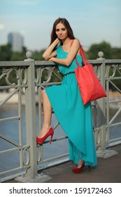 Beautiful girl in a blue summer dress is standing on the bridge