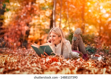 Beautiful girl with book in the autumn park lying in grass